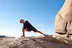 Man in yoga pose bound lunge outdoors in a spectatcular stone landscape.