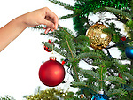 Woman holding Christmas ornament in a hand decorating a Christmas tree