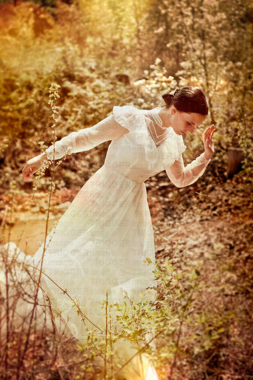 atmospheric photo of beautiful young caucasian woman in white wedding dress between the trees
