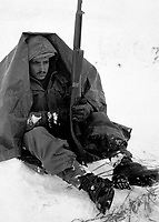 Pfc. Preston McKnight, 19th Inf. Regt., uses his poncho to get protection from the biting wind and cold, in the Yoju area, during break in action against the Chinese Communist aggressors.  Janurary 10, 1951.  Cpl. E. Watson. (Army)<br /> NARA FILE #:  111-SC-356309<br /> WAR &amp; CONFLICT BOOK #:  1393