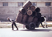 A man carries a wagon of barrels down the street on the outskirts of  Port-au-Prince, Haiti. photo by jane therese