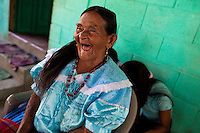 "An old Salvadoran woman laughs, while watching the procession of the Flower & Palm Festival in Panchimalco, El Salvador, 8 May 2011. On the first Sunday of May, the small town of Panchimalco, lying close to San Salvador, celebrates its two patron saints with a spectacular festivity, known as ""Fiesta de las Flores y Palmas"". The origin of this event comes from pre-Columbian Maya culture and used to commemorate the start of the rainy season. Women strip the palm branches and skewer flower blooms on them to create large colorful decoration. In the afternoon procession, lead by a male dance group performing a religious dance-drama inspired by the Spanish Reconquest, large altars adorned with flowers are slowly carried by women, dressed in typical costumes, through the steep streets of the town."