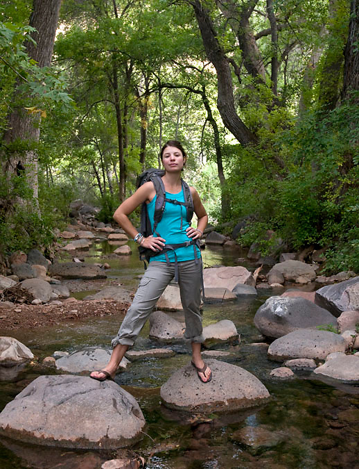 A proud and confident woman straddles two rocks at Fossil Springs, where several large springs erupt out of a dry creek bed forming Fossil Creek.