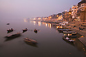 Boats on the Ganges River near the Ghats (stairs) at dawn;  Varanasi has been a cultural and religious center in northern India for several thousand years, Varanasi, Uttar Pradesh, India
