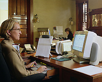 Female office worker using computer to assist her tasks. Model released.