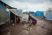 ARBAT, IRAQ: Refugees in a camp on the outskirts of Arbat in the semi autonomous region of Iraqi Kurdistan dig channels to try and direct water away from their tents. ..Refugees from Syria, most of whom are Kurds, have been arriving at camps in Kurdistan trying to escape the continuing conflict.  Arbat is located approximately 20 kilometres away from Sulaimaniyah...Photo by Ali Arkady/Metrography.