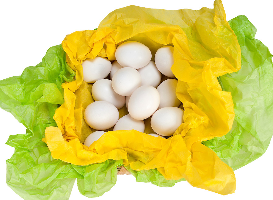 Natural basket with eggs and tissue paper in green and yellow.