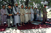 Warlord Ahmad Shah Massoud praying with is commanders and locals outside is office in Khoaja Bahauddin few days before is assassination in the same house (Massoud is the fifth from the right)..Ahmed Shah Massoud was born in Jangalak in the Panjshir Valley in 1953. He attended the university in Kabul where he studied engineering. The invasion of Afghanistan by the Soviet Union in 1979 changed the course of Ahmed Shah Massoud's life. .Massoud become a Mujahidin in the 80 and one of the most brilliant military strategists. Arrive the 90 and the civil war, Massoud turn in to a warlord, how loot and kill thousands of Afghan Muslim civilians. .He die the 09 September 2001 in the explosion of a camera with two fake journalist.