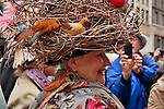A woman wears a hat that looks like a large bird's nest to the Easter Parade in New York City on Fifth Avenue