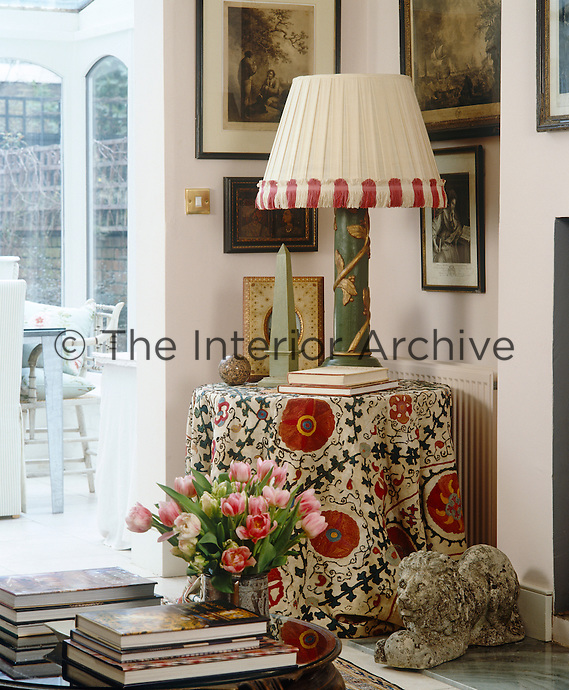 Creating an interesting corner in this living room a round table is covered in an Uzbek suzani