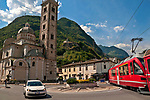 Basilica della Madonna di Tirano church on the left, the Church of St. Perpetua up on the hill, and the Bernina Express Swiss train passing through Tirano, Italy where it starts the trip up to St. Mortiz, Switzerland