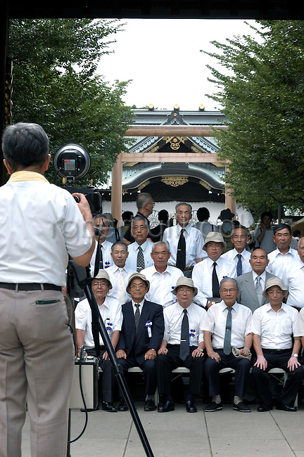 Visitors have a commemorative photo taken at Yasukuni Shrine in Tokyo, Japan...very year on August 15, the day Japan officially surrendered in WWII, tens of thousands of Japanese visit the controversial shrine to pay their respects to the 2.46 million war dead enshrined there, the majority of which are soldiers and others killed in WWII and including 14 Class A convicted war criminals, such as Japan's war-time prime minister Hideki Tojo. Each year speculation escalates as to whether the country's political leaders will visit the shrine, the last to do so being Junichiro Koizumi in 2005. Nationalism in Japan is reportedly on the rise, while sentiment against the nation by countries that suffered from Japan's wartime brutality, such as China, has been further aggravated by Japan's insistence on glossing over its wartime atrocities in school text books...Photographer:Robert Gilhooly..