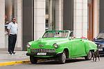 Havana, Cuba; a neon green, classic Studebaker parked on the street in Old Havana