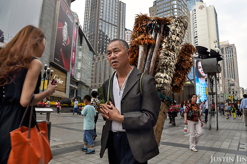Liu Yong, a 59-year-old former farmer, ekes out a living in the city selling chicken-feather brushes in the centre of a Southwestern Chinese city.  <br /> <br /> He earns around 1,000 yuan a month selling these products, made of feathers he collects from chicken farms. <br /> <br /> His village was razed down several years ago by the government and has since lived in resettlement housing on the edge of the metropolis. <br /> <br /> China is pushing ahead with a dramatic, history-making plan to move 100 million rural residents into towns and cities between 2014 and 2020 &mdash; but without a clear idea of how to pay for the gargantuan undertaking or whether the farmers involved want to move.<br /> <br /> Moving farmers to urban areas is touted as a way of changing China&rsquo;s economic structure, with growth based on domestic demand for products instead of exporting them. In theory, new urbanites mean vast new opportunities for construction firms, public transportation, utilities and appliance makers, and a break from the cycle of farmers consuming only what they produce.<br /> <br /> Urbanization has already proven to be one of the most wrenching changes in China&rsquo;s 35 years of economic reforms. Land disputes rising from urbanization account for tens of thousands of protests each year.