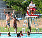 WATERBURY, CT. 27 July 2010-072710SV05--From left; Jorge A. Cruz, 11, of Waterbury and John Enwerem, 10 of Waterbury jump into the pool as head lifeguard Craig Poulter watches at the Hamilton Park pool in Waterbury Tuesday.<br /> Steven Valenti Republican-American