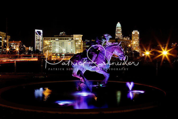 """The Captain Jack Statue """"The Spirit of Mecklenburg"""" glows before the nighttime Charlotte skyline. The statue was created by The May 20th Society, an organization dedicated to the 1775 signing of the Mecklenburg Declaration of Independence. Artist Chas Fagan created the statue, which is located on the Little Sugar Creek Greenway at the corner of 4th Street and Kings Drive."""