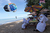 Malaysia, Penang. Batu Ferringhi. Nuns watching parasailing at the beach.
