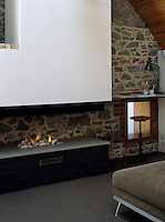 A modern fireplace with a gas fire dominates the stone wall at one end of this mezzanine living room