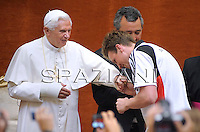 Pope Benedict XVI wears a cap as others applaud including Paul Biedermann of Germany who handed hover the present to his holiness, gold medallist in the men's 200m freestyle during the audience for competitors of the Rome world swimming championships outside of his summer residence in Castelgandolfo, South of Rome on August 1, 2009..