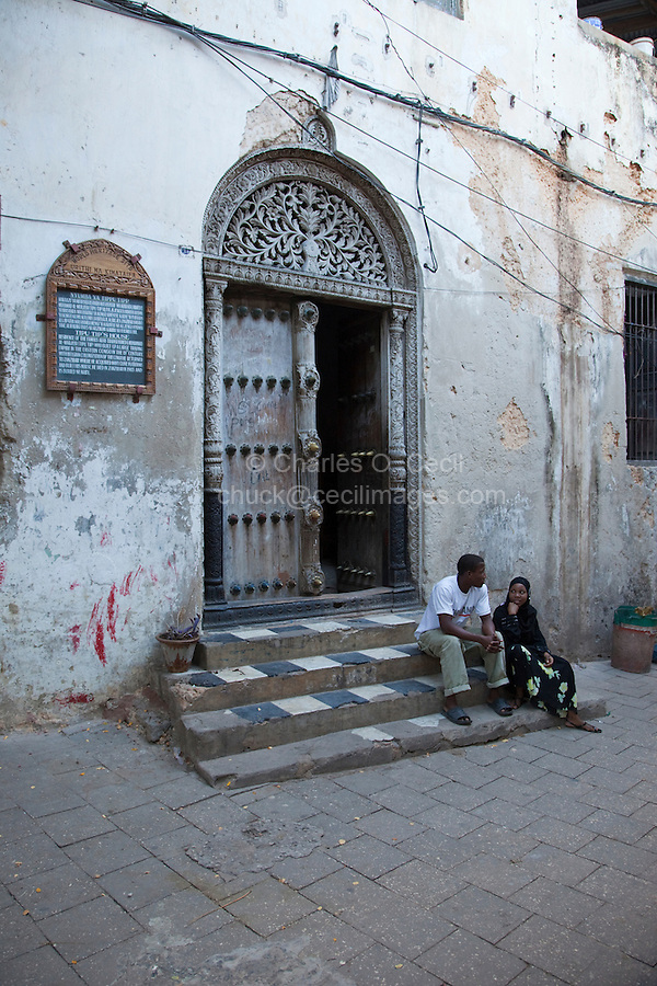 Stone Town, Zanzibar, Tanzania.  Entrance to Tippu Tip's House.  Indian-style Carving above the Door.  Woman wearing a buibui, the traditional black covering over a more colorful garment underneath.  The man wears typical Western, or European, clothes.