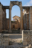 Low angle view of an arch in the Frigidarium of the Baths of Licinius, 3rd century, with the Capitol in the background, in Dougga, Tunisia, pictured on January 31, 2008, in the afternoon. Dougga has been occupied since the 2nd Millennium BC, well before the Phoenicians arrived in Tunisia. It was ruled by Carthage from the 4th century BC, then by Numidians, who called it Thugga and finally taken over by the Romans in the 2nd century. Situated in the north of Tunisia, the site became a UNESCO World Heritage Site in 1997. The Baths of Licinius or the Winter Baths were constructed in 260 A.D. The bathing complex had marble walls and mosaic floor. It featured all the comforts of a classical Roman bath: a Frigidarium (cold room) in the center, Tepidarium (water bath), Caldarium (hot bath), Palaestra (gym), lavatory and a Sudatorium (sweat bath). Picture by Manuel Cohen.