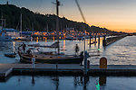 A sailboat arrives at the transit dock at Port Angeles marina at dusk.