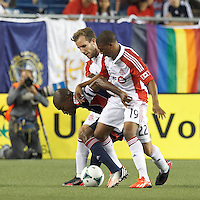Toronto FC midfielder Reggie Lambe (19) and Toronto FC forward Jeremy Brockie (22) double-team New England Revolution defender Jose Goncalves (23). In a Major League Soccer (MLS) match, Toronto FC (white/red) defeated the New England Revolution (blue), 1-0, at Gillette Stadium on August 4, 2013.