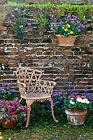 Wrought iron chair with potted plants against old brick wall, LA USA