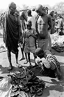 Ethiopia. South Omo Zone. Salamago district. Hana (little village). Bodi tribe. Nomadic. Every sunday morning is market day. Bodi, Dime, Mursi and Amhara come to buy food items, clothes, shoes, tobacco,.. Bodi, Dime, Mursi and Amhara are four diverse tribes of Ethiopia. An almost naked bodi man looks at the leather shoes. The Bodi tribe is located in the Debub Omo Zone (South Omo Zone) of the Southern Nations, Nationalities and Peoples's région. © 2001 Didier Ruef