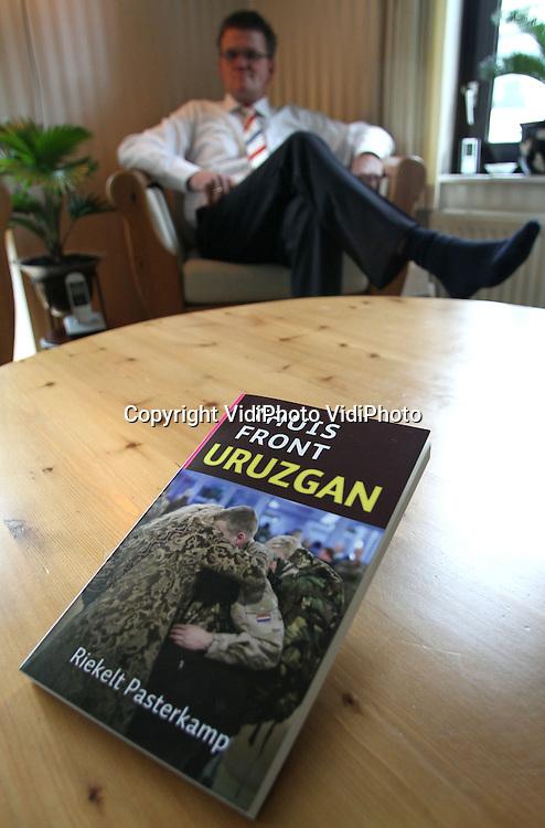 """Foto: VidiPhoto..APELDOORN - Freelance-journalist en auteur Riekelt Pasterkamp uit Apeldoorn toont woensdag het boek over Uruzgan dat hij zaterdag op Urk presenteert. Het boek, met de titel """"Thuisfront Uruzgan"""" staat vol met interviews met ouders van militairen die in Uruzgan waren, inclusief ouders die daar een kind verloren. In """"Thuisfront Uruzgan"""" staan ook interviews met de generaals Marc en Peter van Uhm. Peter van Uhm verloor in 2008 zijn zoon in Uruzgan. Uitgever is Kok Kampen"""