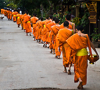 Monks with their alms bowls move along the road towards the end of their morning collection. (Photo by Matt Considine - Images of Asia Collection)