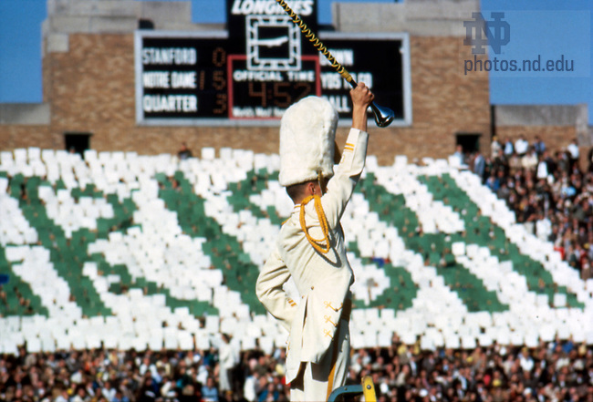 GPUB 28/25:  Football Game Scene - Notre Dame vs. Stanford, 1964/1024.  Marching Band Drum Major inside Notre Dame Stadium while fans hold cards that spell out &quot;Irish&quot; in the background.<br /> Photo by Bruce Harlan, University Photographer.  Image from the University of Notre Dame Archives.