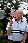 Elderly man blowing bubbles in backyard Marysville Washington State USA  MR