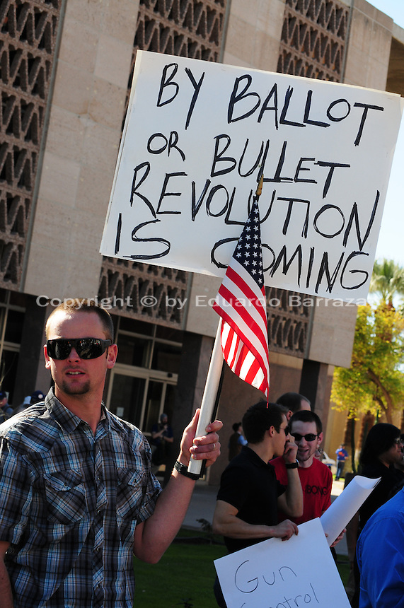 """Phoenix, Arizona. January 19, 2013 - A protester holds a sign to oppose the president proposed changes to gun laws in America. As President Barack Obama proposed new gun regulations last week, gun owners demonstrated against it with national """"Guns Across America"""" rallies to defend the Second Amendment. Dozens showed up at the Arizona State Capitol, many of them carrying weapons. Photo by Eduardo Barraza © 2013"""