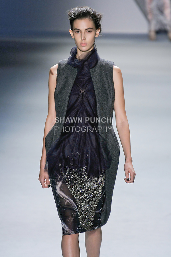 Ruby Aldridge walks runway in a charcoal melton cutaway high-low vest over plum silk chiffon multi-layer silk tulle flange top, with black vault print silk chiffon skirt with crystal mesh overlay, from the Vera Wang Fall 2012 Vis-a-gris collection, during Mercedes-Benz Fashion Week Fall 2012 in New York.