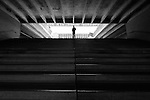 A lone silhouetted man standing at the top of a staircase, centered.