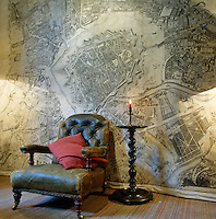 An old map on fabric hangs behind a well-worn leather armchair