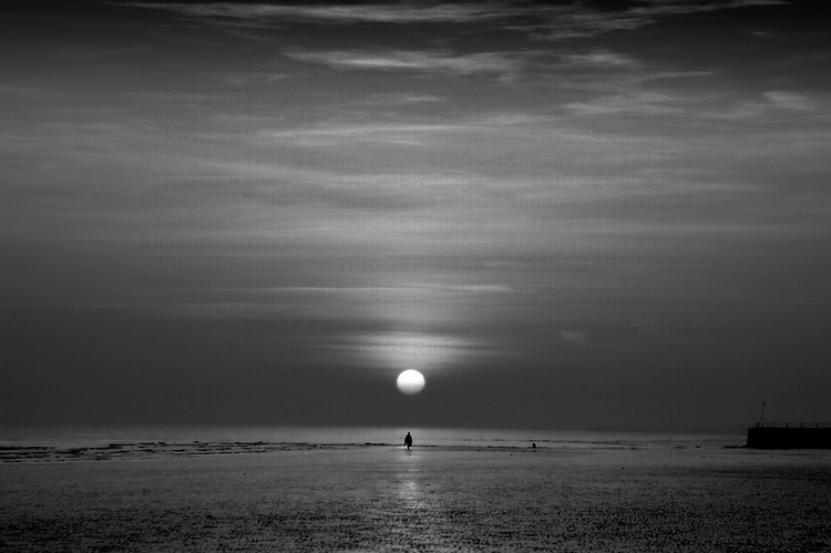 A lone figure in the distance below a setting sun on a deserted beach, England