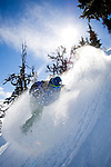 A snowboarder rides some powder on Whistler Mountain, BC. Canada.
