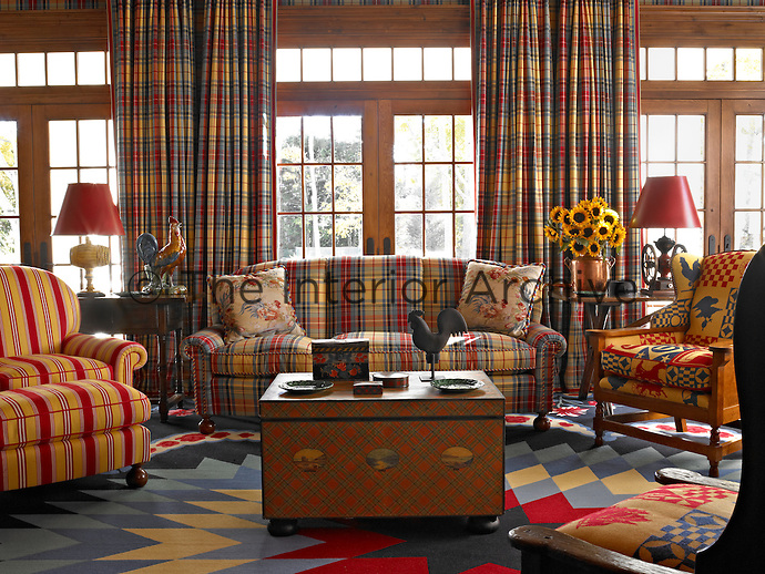 The living room is a riot of tartan, stripes and florals all arranged on a modern multi-coloured rug designed in a series of lozenge shapes radiating from a central star