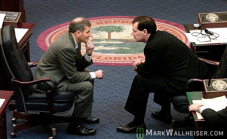 Florida Representative Mike Fasano (L) R-New Port Richie and House Majority Leader and Florida Representative Johnnie Byrd, R-Plant City and Chairman of the Procedural Council, lean out into the center isle of the Florida House of Representatives to talk during todays session Dec 12, 2000.  Today's session of the special session of the House wasto hear the pros and cons on selecting Republican electors to vote for George W. Bush.