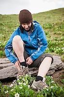Female hiker ties shoes while sitting on rock, Ice Lakes basin, San Juan Mountains, Colorado, USA