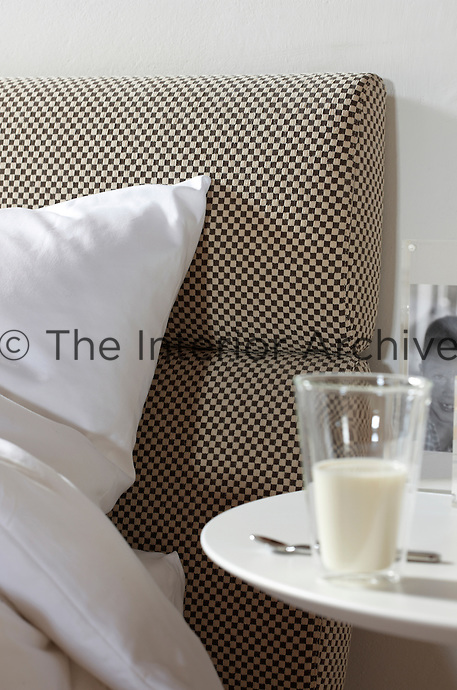 The contemporary bed has a brown and beige checked fabric headboard