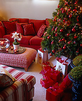 Presents are arranged at the base of an imposing Christmas tree decorated with red glass baubles