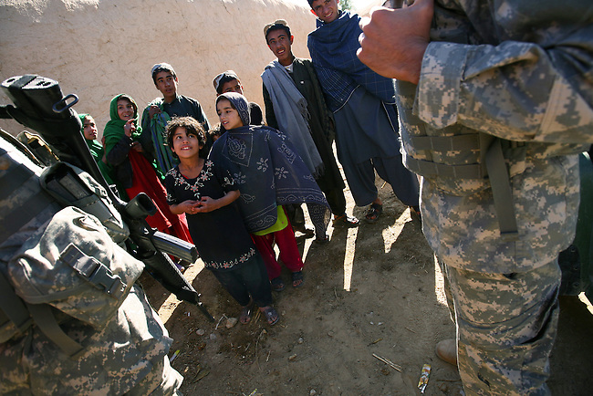 Children in the village of Pir Zadeh in Maiwand district, Kandahar province, Afghanistan gather around a U.S. soldier and interpreter as troops from 2nd Battalion, 2nd Infantry Regiment hand out food staples and warm clothes to villagers. Jan. 4, 2009. DREW BROWN/STARS AND STRIPES