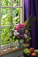 A green and white spotted jug on the window sill contains a bouquet of flowers and ferns from the garden