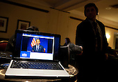 Reporters record United States President Barack Obama who is shown on the screen of a laptop computer as he speaks during a video teleconference with Iowa Caucus attendees from Washington, D.C. on Tuesday, January 3, 2012. .Credit: Joshua Roberts / Pool via CNP