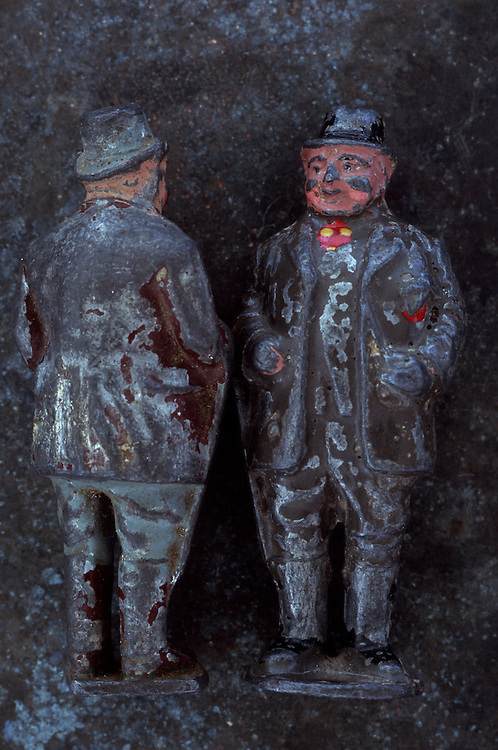 Worn lead models of two almost identical rotund 19th century farmers standing side-by-side against mottled metal background