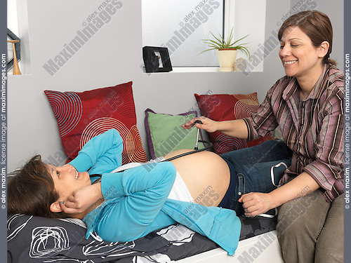 Pregnant young woman listening to her baby's heartbeat with a midwife's assistance