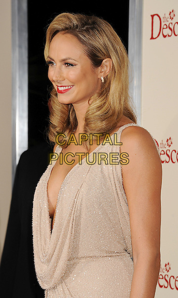 Stacy Keibler.Premiere of 'The Descendants' held at The Academy of Motion Pictures, Arts & Sciences in Beverly Hills, California, USA..November 15th, 2011.half length beige cream dress cowl neck low cut plunging neckline cleavage side profile.CAP/ROT/TM.©Tony Michaels/Roth Stock/Capital Pictures
